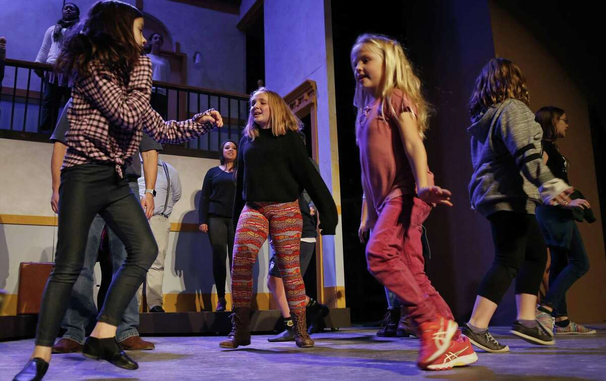 """Alex Phillips, center, rehearses a scene for the Woodlawn Theatre's production of """"Annie."""""""