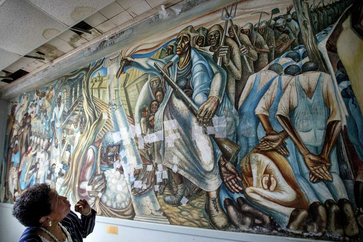 """Charlotte Bryant looks at the John Biggers mural, """"Contribution of Negro Women to American Life and Education"""" that was damaged in the aftermath of Hurricane Harvey, at the Blue Triangle Community Center on Wednesday, Nov. 7, 2018, in Houston. The historic mural was temporarily treated to prevent mold from spreading across it, but still needs extensive work to fully restore the work of art and the building in which it is housed."""