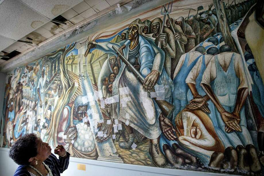 "Charlotte Bryant looks at the John Biggers mural, ""Contribution of Negro Women to American Life and Education"" that was damaged in the aftermath of Hurricane Harvey, at the Blue Triangle Community Center on Wednesday, Nov. 7, 2018, in Houston. The historic mural was temporarily treated to prevent mold from spreading across it, but still needs extensive work to fully restore the work of art and the building in which it is housed. Photo: Brett Coomer,  Houston Chronicle / Staff Photographer / © 2018 Houston Chronicle"