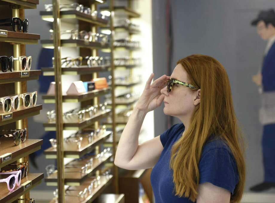 Darien resident Tricia Finnegan tries on sunglasses in July 2018 at the new Warby Parker store on Greenwich Avenue in Greenwich, Conn., the retailer's first location in the state. Photo: Tyler Sizemore / Hearst Connecticut Media / Greenwich Time