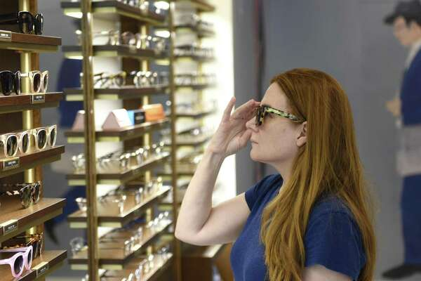 Darien resident Tricia Finnegan tries on sunglasses in July 2018 at the new Warby Parker store on Greenwich Avenue in Greenwich, Conn., the retailer's first location in the state.