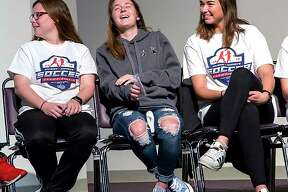 LCCC soccer player Claire Dalton, center laughs during Monday's ceremony honoring the team, which finished 19-1 and advanced to the NJCAA National Tournament. Dalton, a sophomore from Marquette Catholic High, is flanked by teammates Samantha Eckert, left, and Allie Smith.
