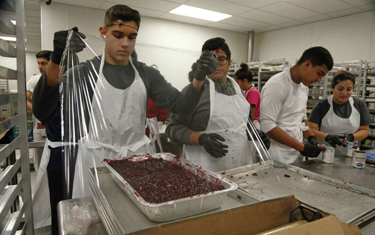 Abraham Guardia, 15, prepares to cover cranberries. Jimenez Thanksgiving Dinner prep work. Volunteers are assembling 9,400 pounds of turkey, 6,250 pounds of green beans, 4,688 pounds