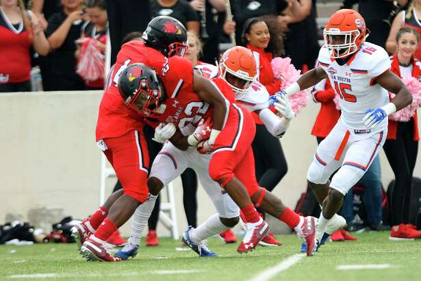 Lamar running back Myles Wanza is tackled by Sam Houston linebacker Evrin Hawkins at Provost Umphrey Stadium on Saturday. Photo taken Saturday 10/20/18 Ryan Pelham/The Enterprise