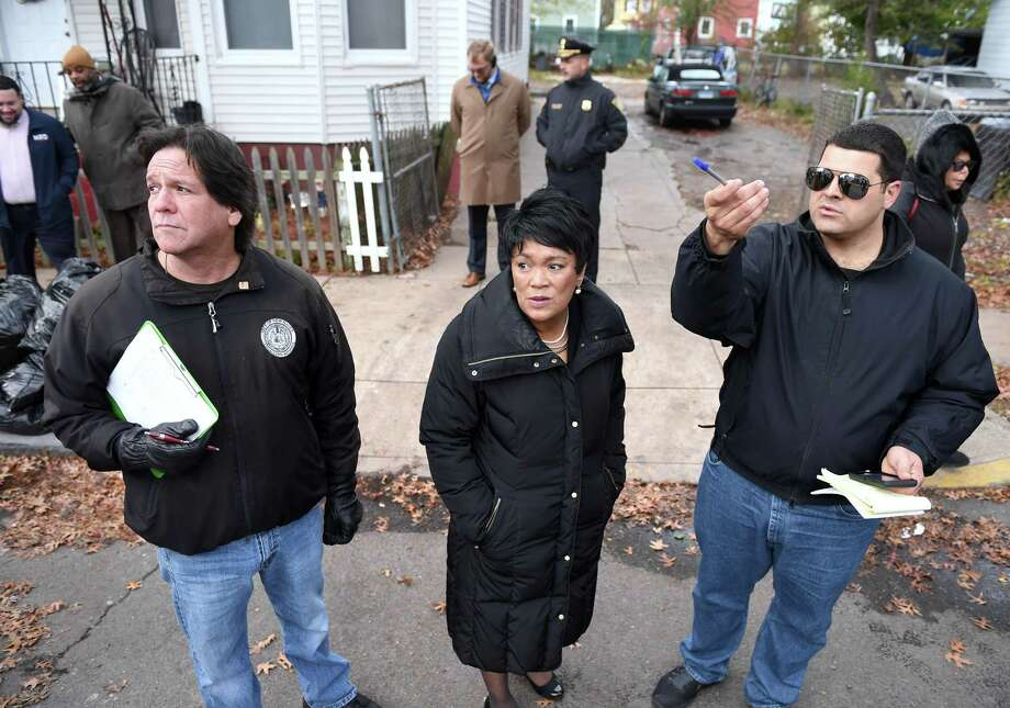 "Livable City Initiative housing code inspector Rickie Mazzadra, left, and Arthur Natalino, Jr., right, LCI Hill Section neighborhood specialist, join New Haven Mayor Toni Harp and other city department personnel in a ""clean and safe"" tour of the Hill South section of New Haven on Nov. 14, 2018. Photo: Arnold Gold / Hearst Connecticut Media / New Haven Register"