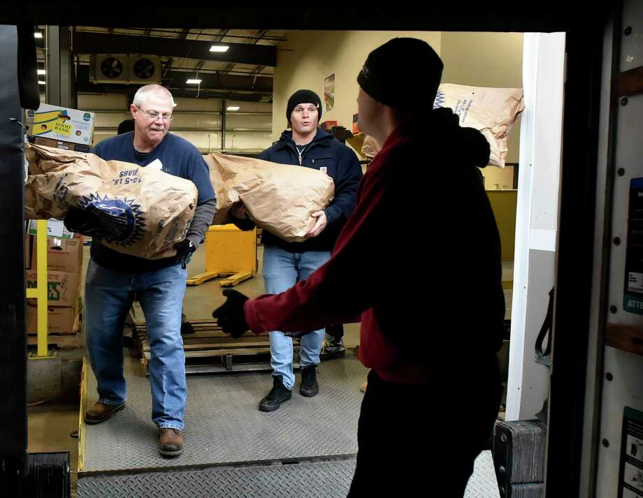 Wallingford, Connecticut - November 19, 2018: Coast Guardsmen  Chief Roger Faber, left, and Petty Officer Third Class Sean Keating, center, are among  22 U.S. Coast Guard volunteers from Coast Guard Sector Long Island Sound of New Haven that helped fill community food program Thanksgiving orders and load the food orders in vehicles  Monday at the Connecticut food Bank in Wallingford for Connecticut Food Bank member agencies. Photo: Peter Hvizdak, Hearst Connecticut Media / New Haven Register