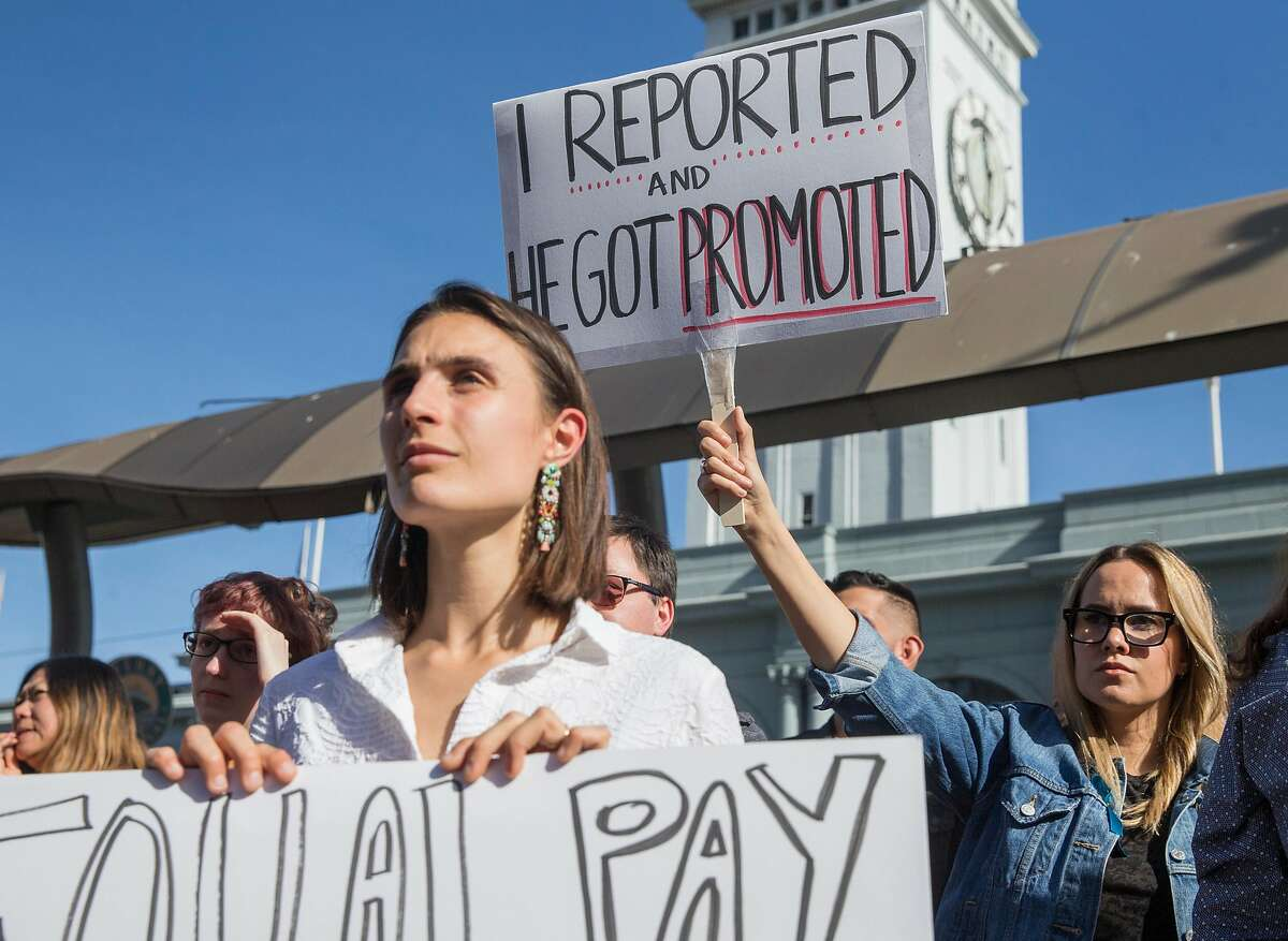 Google employees Lucia Rossazza, left, and Jennifer Brown, right, carry signs while listening to speakers during a rally and company-wide walkout and from their offices in San Francisco, Calif. Thursday, Nov. 1, 2018 highlighting the mishandling by the company of sexual misconduct allegations.