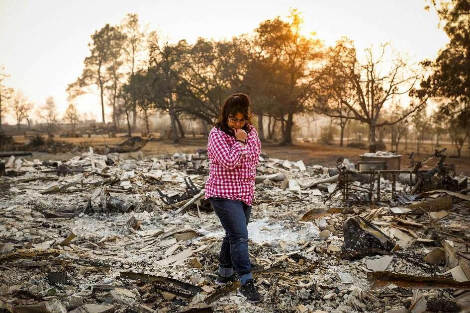 Catherine Wiggins, 57, walks through her property after the Camp Fire destroyed her home in Paradise, California, on Monday, Nov. 19, 2018.