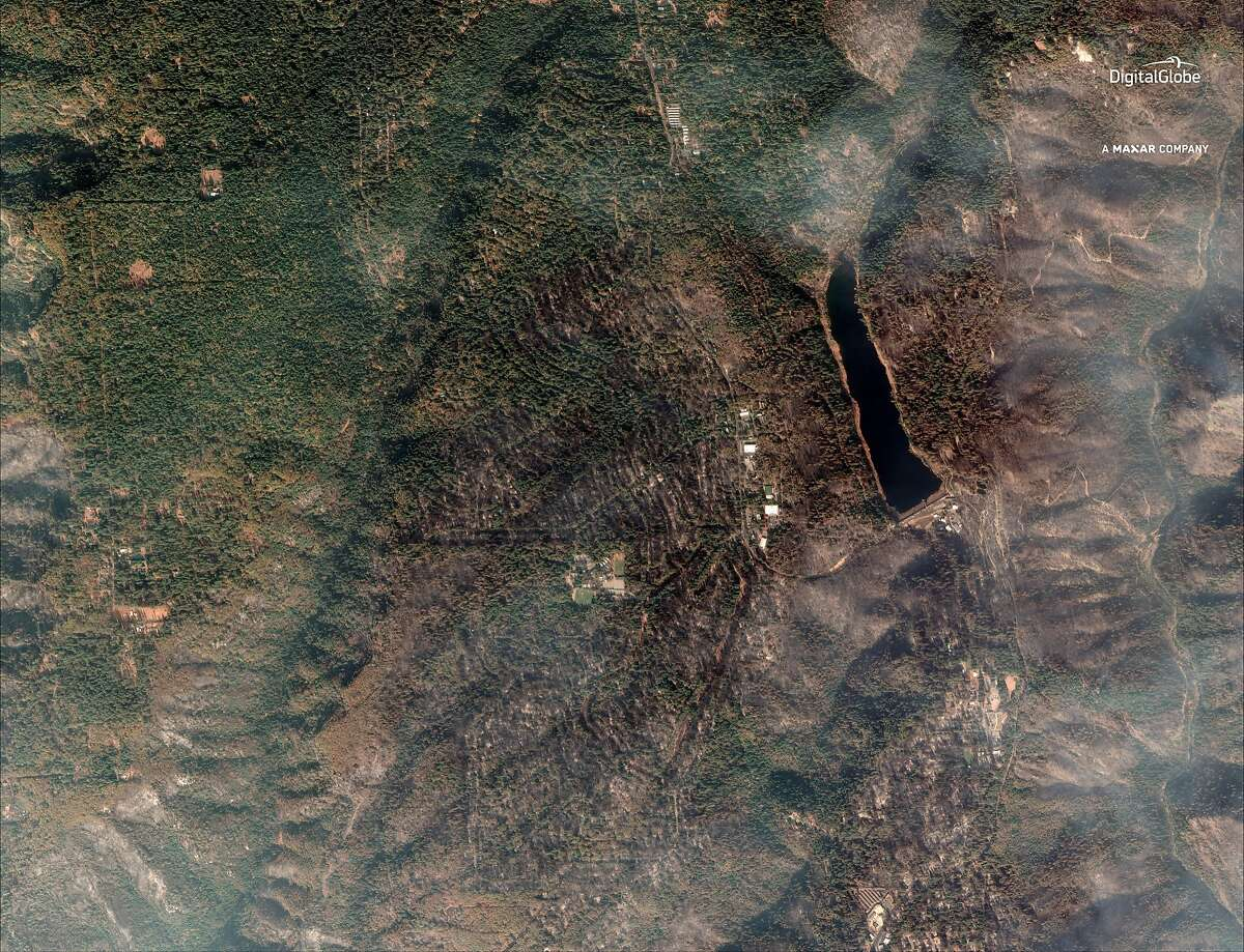This Sept. 10, 2018, satellite image provided by DigitalGlobe shows part of Magalia, situated around Magalia Reservoir, center right, north of Paradise in northern California after a wildfire. Desperate families posted photos and messages on social media and at shelters in hopes of finding missing loved ones, many of them elderly, nearly two weeks after the wildfire known as the Camp Fire. (DigitalGlobe, a Maxar company via AP)