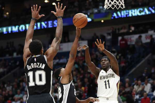 New Orleans Pelicans guard Jrue Holiday (11) passes between San Antonio Spurs guard DeMar DeRozan (10) and forward Rudy Gay (22) in the first half of an NBA basketball game in New Orleans, Monday, Nov. 19, 2018. (AP Photo/Gerald Herbert)