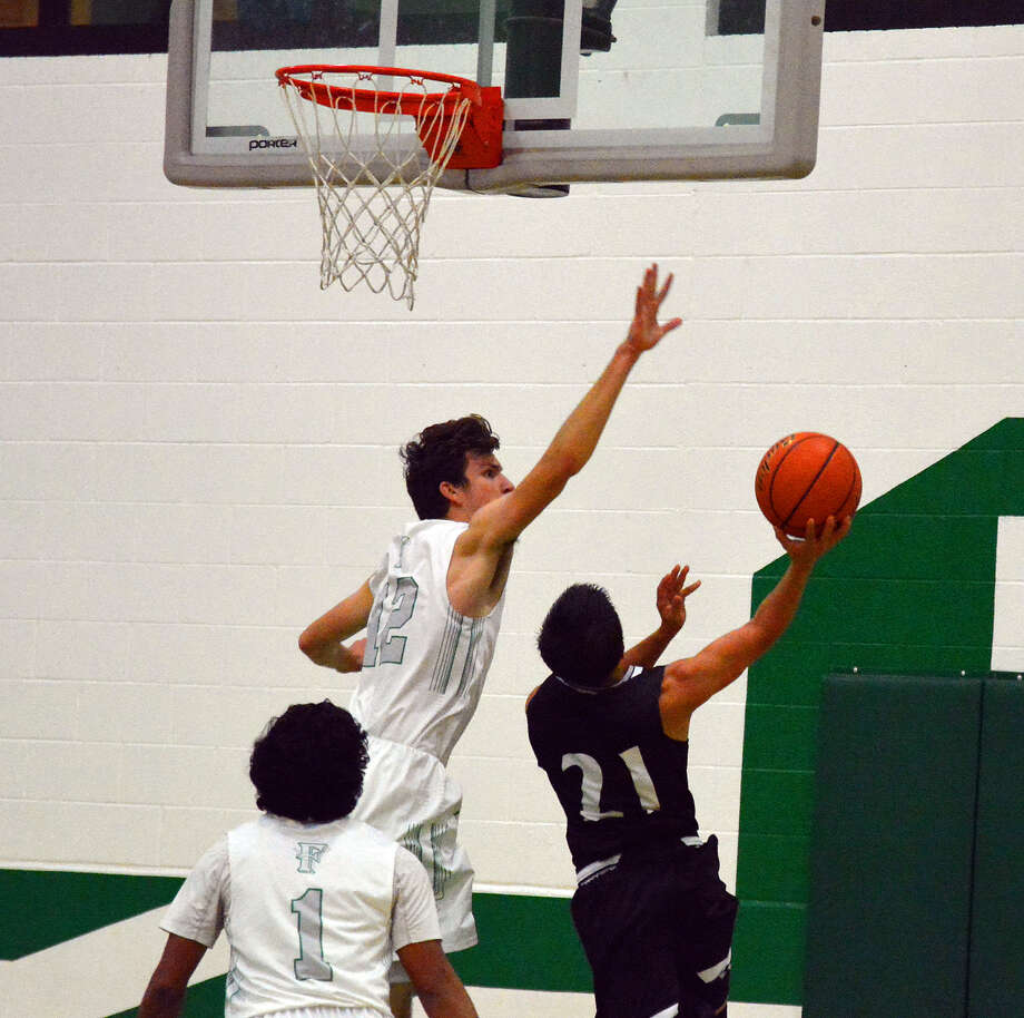 REJECTED  Floydada senior center Caden Britt (12) blocks Muleshoe guard Derek Barron's shot during the Whirlwinds basketball season opener on Monday in Floydada. Britt had three blocks as the Whirlwinds beat the Mules, 81-65. Photo: Alexis Cubit/Plainview Herald