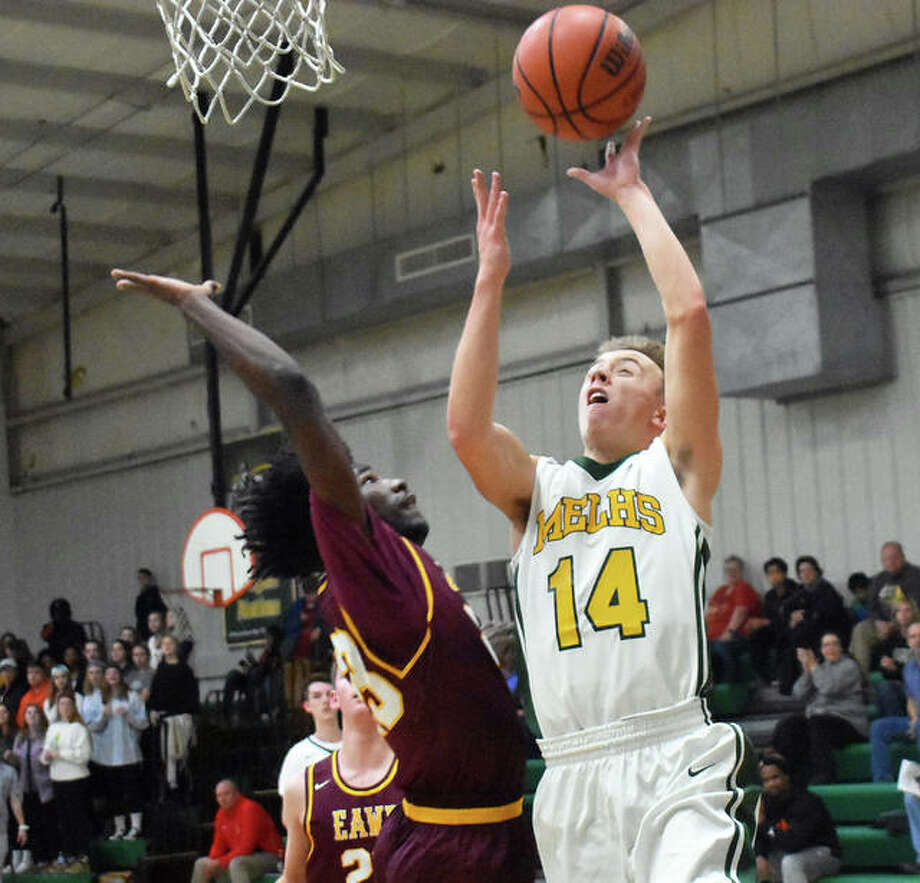 Metro-East Lutheran's Jonah Wilson, left, goes up for a layup during the first quarter against East Alton-Wood River. Photo: Matt Kamp/Intelligencer