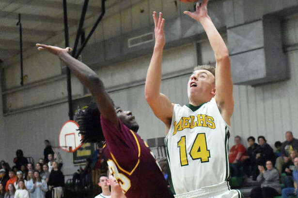 Metro-East Lutheran's Jonah Wilson, left, goes up for a layup during the first quarter against East Alton-Wood River.