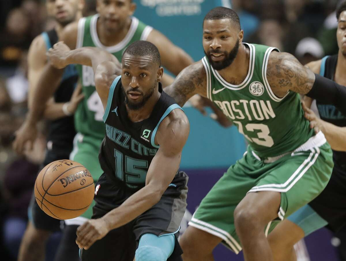 Charlotte Hornets' Kemba Walker (15) steals the ball from Boston Celtics' Marcus Morris (13) during the second half of an NBA basketball game in Charlotte, N.C., Monday, Nov. 19, 2018. (AP Photo/Chuck Burton)