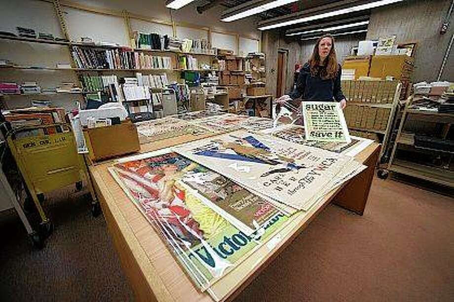 Angela Bonnell, head of government documents at Illinois State University's Milner Library, talks about a World War I-era poster from the U.S. Food Administration. The posters promoted the rationing of sugar as part of the war effort. Photo: Lewis Marien | The Pantagraph (AP)