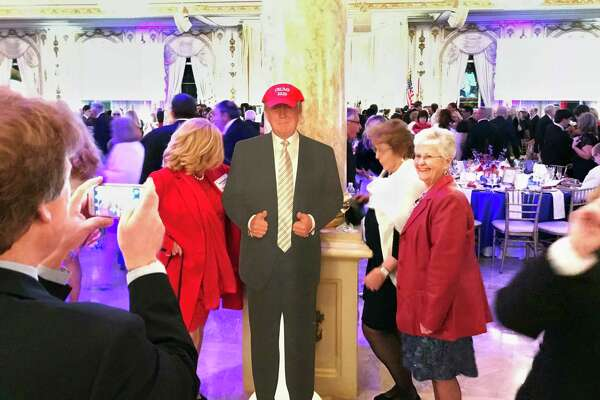 "Supporters of President Donald Trump pose with a cardboard cutout at the entrance to the Donald J. Trump Grand Ballroom at Trump's Mar-a-Lago Club in Palm Beach, Florida, on Jan. 18, 2018. The event was put on by the ""Trumpettes USA."""