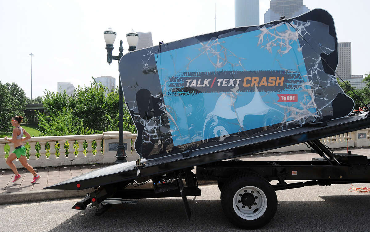 A jogger runs past an oversized cell phone on the Sabine Street bridge. The phone is part of the Talk,Text, Crash campaign that is designed to call attention to the epidemic of driver distractions in Texas.