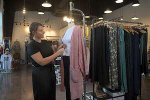 Owner Nicole Christian works a display at Pretty Little Things Boutique in Kings Harbor in Kingwood on Hov. 16, 2018.