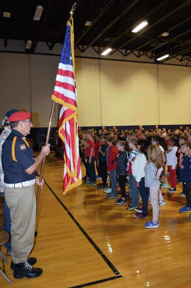 "Spectrum/The Sarah Noble Intermediate School community in New Milford recently recognized Veterans Day with several events. Several classrooms had visits by local veterans, many of them relatives of students in their respective classroom. In addition, veterans were invited to attend a special breakfast and participate in three assemblies one for each grade level held in the multi-purpose room. Students also showcased their pride for loved ones and friends who have served by displaying veterans names, ranks and photographs on boards near the main office. Above, veteran Bob Greco, who served in the Navy from 1969-72, proudly carries the flag as students sing the ""National Anthem."" 11/9/18 Photo: Deborah Rose / Hearst Connecticut Media / The News-Times  / Spectrum"
