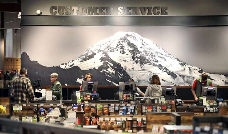 In this photo taken Nov. 13, 2018, clerks work in front of a large photo of Mount Rainier in REI Co-op's flagship store in Seattle. For the fourth consecutive year, REI said that on the popular Black Friday shopping day it will close all 153 stores, process no online payments and pay more than 12,000 employees, encouraging them to recreate outdoors with friends and family. The company calls it #OptOutside. (AP Photo/Elaine Thompson)