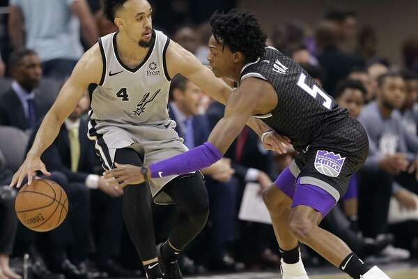 San Antonio Spurs guard Derrick White, left, tries to keep the ball out of the reach of Sacramento Kings guard De'Aaron Fox during the first quarter of an NBA basketball game, Monday, Nov. 12, 2018, in Sacramento, Calif. The Kings won 104-99. (AP Photo/Rich Pedroncelli)