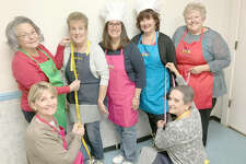"""Making sure their new aprons are """"measuring up"""" for the Dec. 2 Smorgasbord Dinner are seven """"chefs"""" wearing their colorful handmade aprons. Back row, left to right: Fran Nappier, Marge Kirby, Teresa Wilson, Kathy Wilson, Mary Ann Klunk. Kneeling are, left to right: Becky Sulsberger and Bea Albarado. These seven ladies represent various committees that will prepare food for approximately 700 people on Sunday, Dec. 2 from 11 a.m. to 3 p.m. at the Our Lady Queen of Peace Catholic Church, 132 Butcher St. in Bethalto."""
