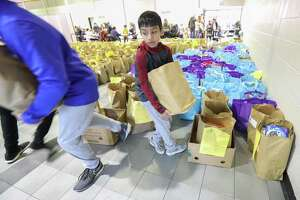 Dilan Dalal, 11, carries bags of food at the East Spring Branch Food Pantry Tuesday, Nov. 20, 2018, in Houston. The food pantry served at least 1,000 families a Thanksgiving meal on Tuesday morning. The pantry provided a turkey (or chicken), a large bag of produce, and bags of non-perishable food to hundreds of families in need.