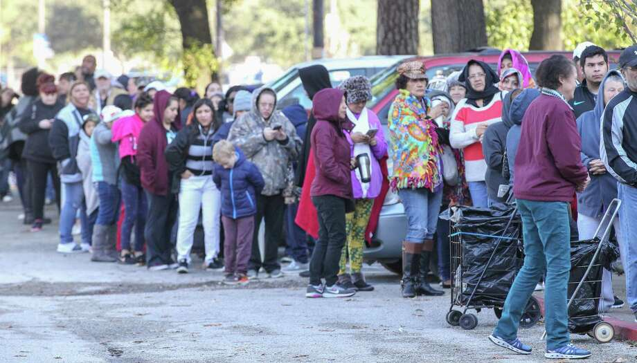 People waited in the cold to receive free food at the East Spring Branch Food Pantry Tuesday, Nov. 20, 2018, in Houston. The food pantry served at least 1,000 families a Thanksgiving meal on Tuesday morning. The pantry provided a turkey (or chicken), a large bag of produce, and bags of non-perishable food to hundreds of families in need. Photo: Steve Gonzales, Houston Chronicle / Staff Photographer / © 2000 Houston Chronicle
