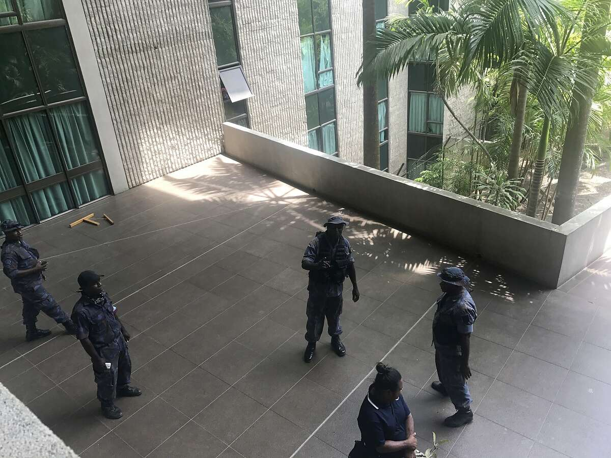 Police and soldiers guard the outside of the Parliament, Tuesday, Nov. 20, 2018, in Port Moresby, Papua New Guinea. Disgruntled police, military and prison guards stormed Papua New Guinea's Parliament on Tuesday in a pay dispute that stemmed from an international summit hosted by the South Pacific island nation over the weekend, a lawmaker said. (Brian Kramer via AP)