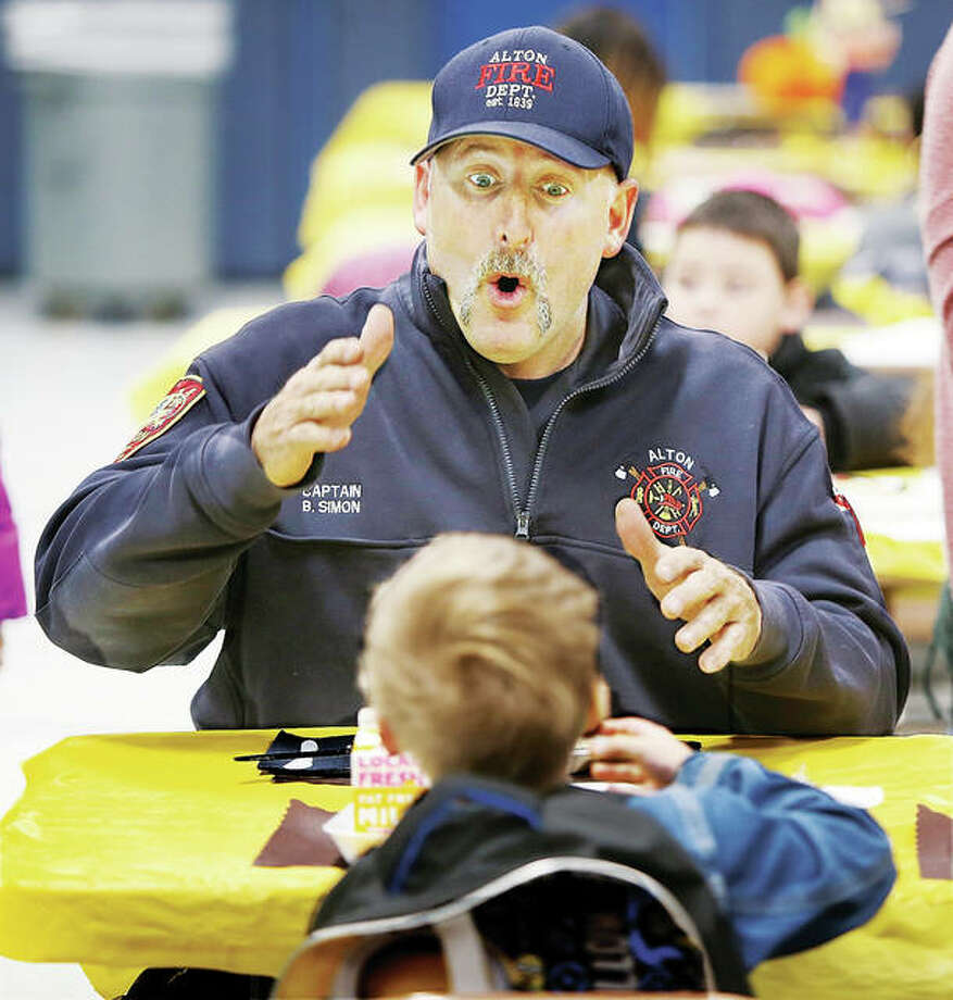 Alton Fire Department Capt. William Simon engages in a conversation with a young student at Eunice Smith School in Alton Tuesday morning during the third annual Breakfast with Buddies program. Photo: John Badman | The Telegraph
