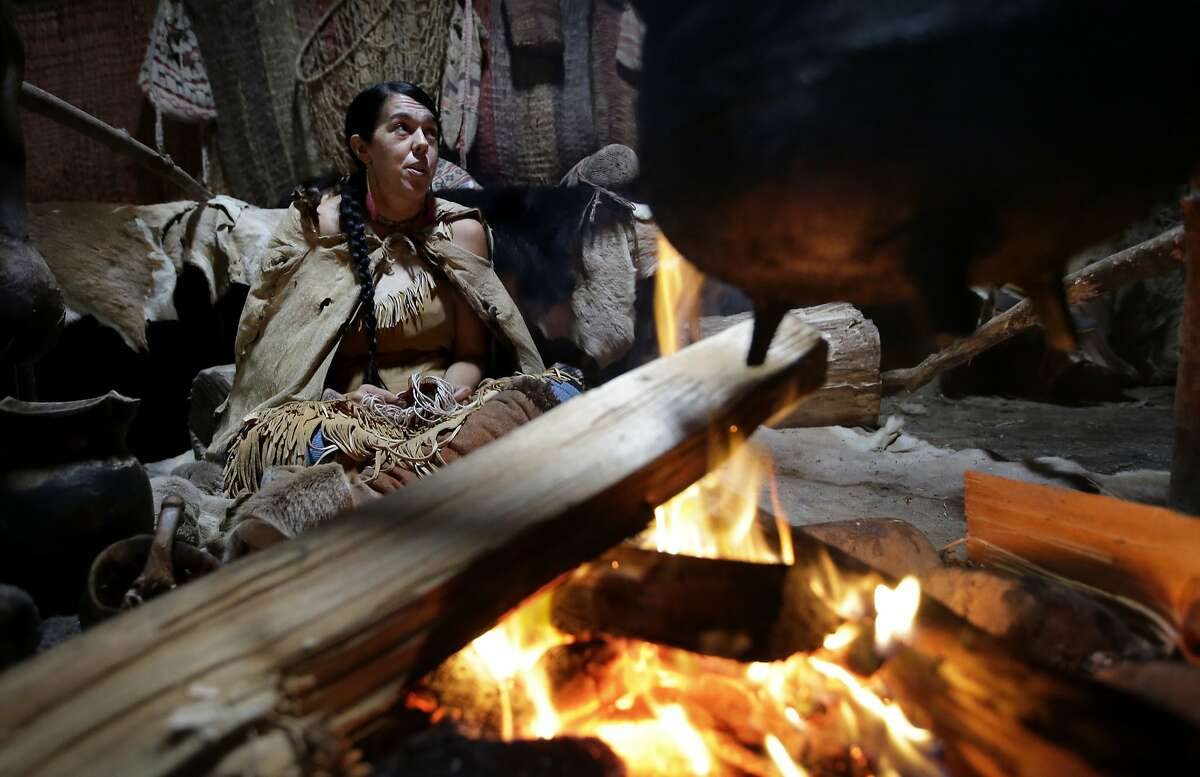 In this Thursday, Nov. 15, 2018, photo, Mashpee Wampanoag Kerri Helme, of Fairhaven, Mass., uses plant fiber to weave a basket while sitting next to a fire at the Wampanoag Homesite at Plimoth Plantation, in Plymouth, Mass. Plymouth, where the Pilgrims came ashore in 1620, is gearing up for a 400th birthday, and everyone's invited, especially the native people whose ancestors wound up losing their land and their lives. (AP Photo/Steven Senne)