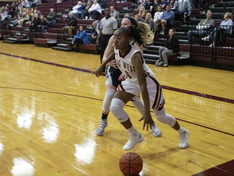 Magnolia West sophomore Kamari Portalis (4) drives past Tombal Memorial senior Breanne Baimbridge (33) during a non-district game Tuesday, Nov. 20, 2018 at Magnolia West High School in Magnolia. Photo: Cody Bahn, Houston Chronicle / Staff Photographer / © 2018 Houston Chronicle