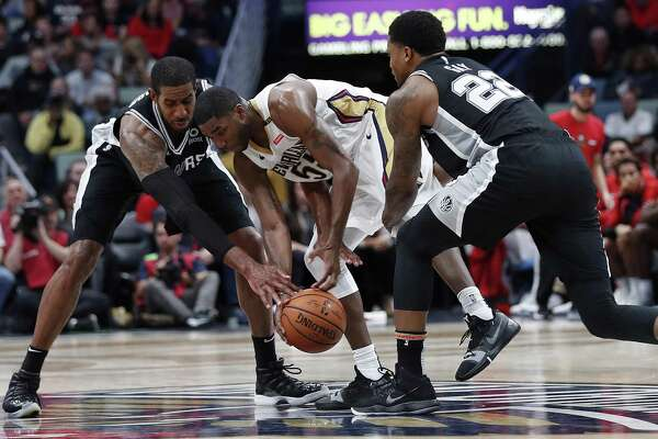 New Orleans Pelicans guard E'Twaun Moore (55) battles for a loose ball with San Antonio Spurs forward Rudy Gay (22) and forward LaMarcus Aldridge in the second half of an NBA basketball game in New Orleans, Monday, Nov. 19, 2018. The Pelicans won 140-126. (AP Photo/Gerald Herbert)