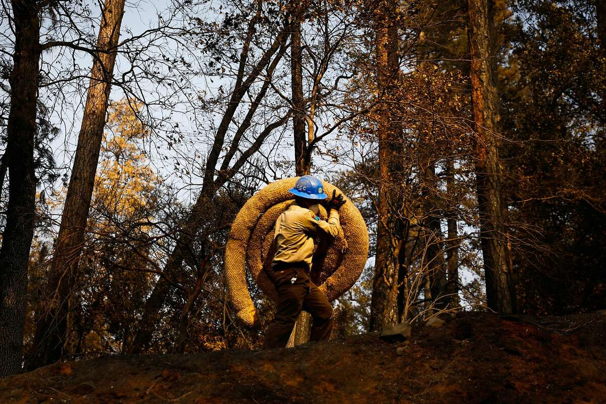 A California Conservation Core member carries up material to help block flooding after the Camp Fire in Paradise, California, on Tuesday, Nov. 20, 2018.