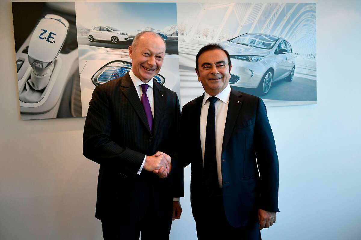 (FILES) In this file photo taken on February 16, 2018 French multinational automobile manufacturer Renault chairman and CEO, Carlos Ghosn (R) and Thierry Bollore, starting February 19, 2018 as deputy director at Renault, shakes hands after a press conference presenting the group's 2017 full year results, at the group's headquarters in Boulogne-Billancourt. - French automaker Renault said on November 20, 2018 it had appointed its chief operating officer as deputy CEO to ensure day-to-day management after the arrest of chief Carlos Ghosn, who will remain chief executive. After an emergency board meeting, Thierry Bollore would become deputy CEO with Ghosn