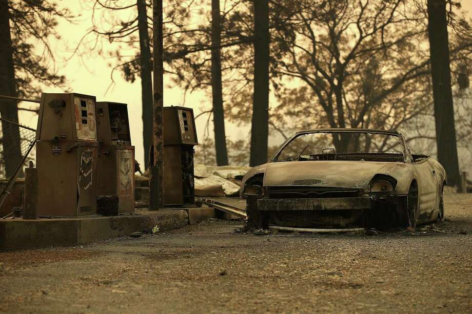 A burned out car sits next gas pumps at a gas station that was destroyed by the Camp Fire on Nov. 11 near Parkhill, California. Fueled by high winds and low humidity the Camp Fire ripped through the town of Paradise charring over 105,000 acres. Photo: Justin Sullivan /Getty Images / 2018 Getty Images
