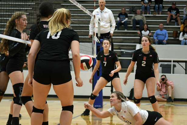 Huffman junior Kenzie Wiggins, bottom, goes to the floor to make a pass against Sweeny during the first set of their UIL Region III Class 6A Area Volleyball Playoff at Phillips Fieldhouse in Pasadena on Nov. 1, 2018.