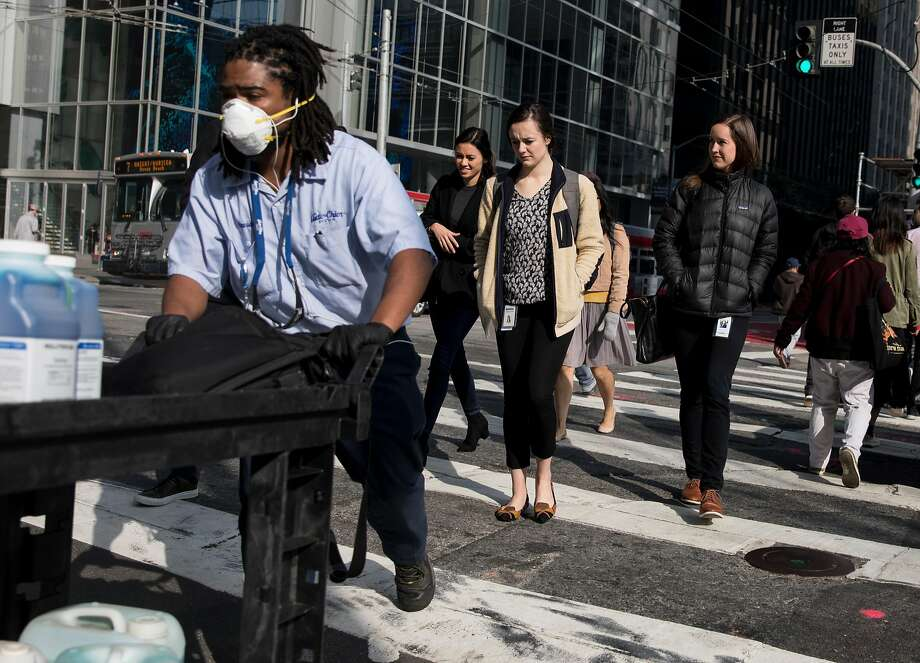 A pedestrian wears a respiratory mask while crossing the street in the South of Market district of San Francisco, Calif. Tuesday, Nov. 20, 2018. Air quality is expected to improve significantly Wednesday as a storm system moves through, but air quality was already noticeably better by Tuesday night as winds began to pick up. Photo: Jessica Christian / The Chronicle