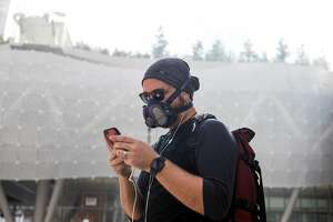 Anselm Engle of Oakland wears a respiratory mask while using his phone in the South of Market district of San Francisco, Calif. Tuesday, Nov. 20, 2018.