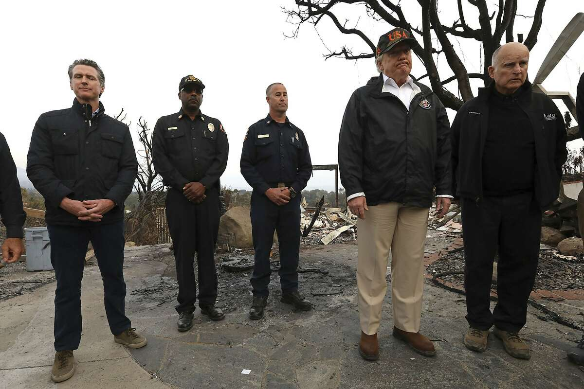 President Donald Trump, second from right, reacts while taking in the damage from the Woolsey Fire alongside California Governor-elect Gavin Newsom, from left, Los Angeles County Fire Chief Daryl Osby, Cal Fire Deputy Chief Nick Schuler and California Governor Jerry Brown in Malibu, Calif., on Saturday, Nov. 17, 2018. Trump arrived at the oceanside conclave Saturday afternoon after visiting Northern California to survey the damage from the Camp Fire in the town of Paradise. (Genaro Molina/Los Angeles Times via AP, Pool)