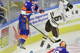 The Sound Tigers' Seth Helgeson, left, checks the Bears' Lucas Johansen off the puck during their AHL game on March 28 at Webster Bank Arena in Bridgeport.