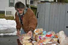 Volunteer Donald Saucier helped arrange bread and desserts for clients who were picking up donated food for Thanksgiving.