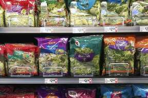 """Bags of Romaine lettuce sit on the shelves Tuesday afternoon at a -H-E-B store in San Antonio, a few hours after the Centers for Disease Control issued a nationwide warning about contamination of the lettuce. An H-E-B spokesman issued a statement: """"We have been working closely with the CDC and suppliers. All Romaine product will be locked at the point of sale. And it will be removed for shelves which is a process, but will not scan at the register."""""""