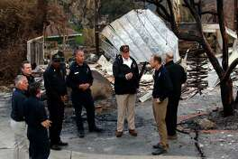 President Donald Trump visits a neighborhood impacted by the Woolsey Fire, Saturday, Nov. 17, 2018, in Malibu, Calif. Looking at the damage at far right is California Gov. Jerry Brown and Gov.-elect Gavin Newsom is third from left. (AP Photo/Evan Vucci)