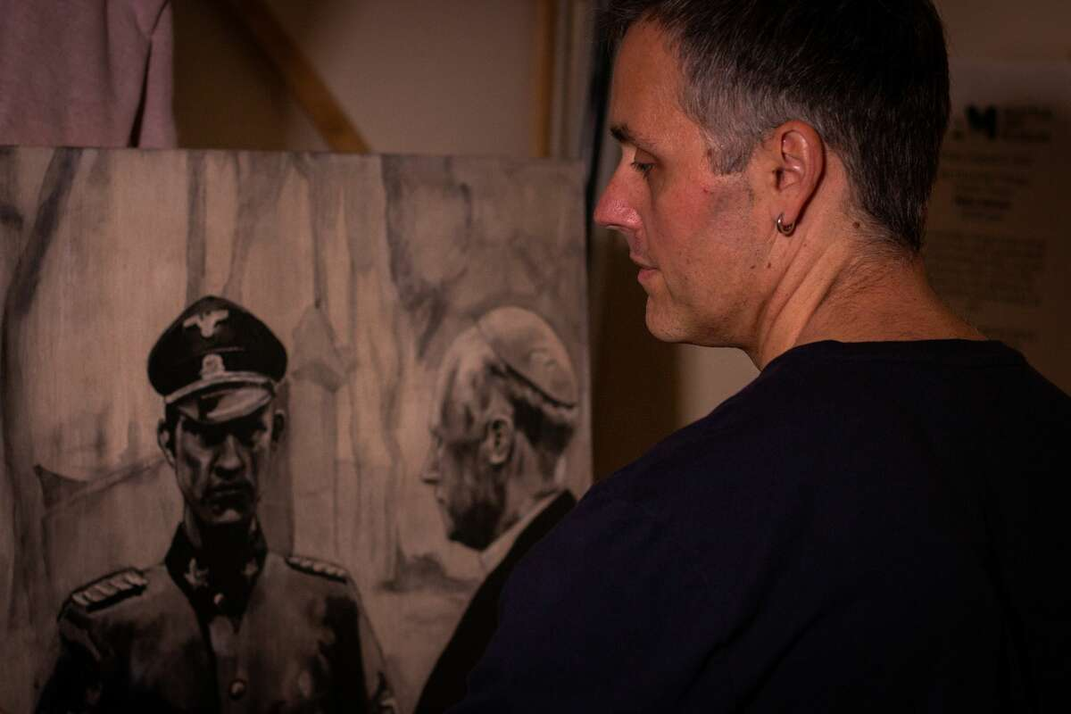 """Artist Miha Sarani works on his painting """"Large Panel I"""" on Nov. 10, 2018, which is the centerpiece of his new series that focuses on war atrocities committed in Yugoslavia during World War II. This painting features Catholic Bishop Gregorij Rožman, whose post-war conviction was overturned years later despite his anti-Semitism and collaboration with Nazi Germany."""