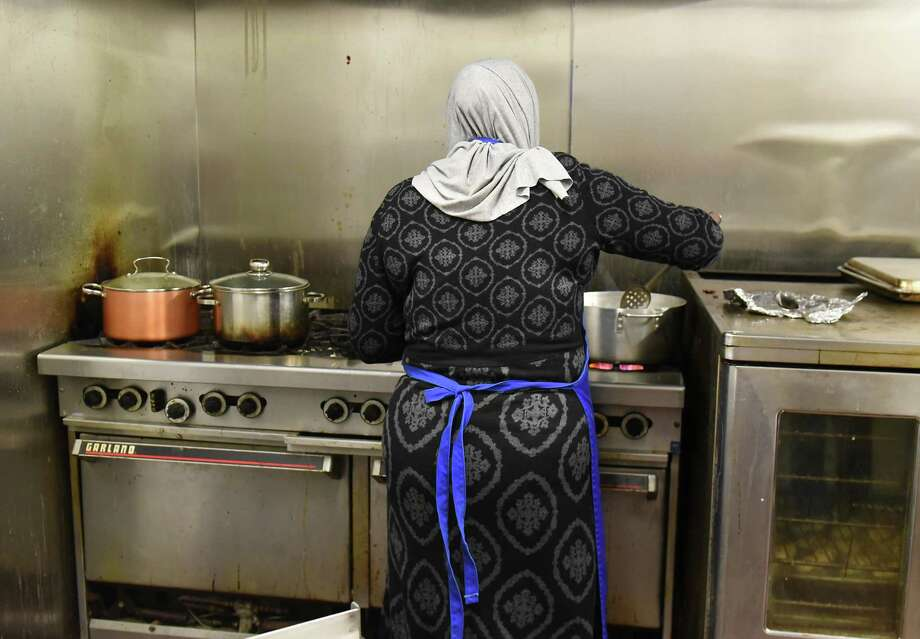 Mariam, one of several Syrian refugee women who started a catering business to support their families, makes kibbeh on the stove for their Thanksgiving order at the Sister Maureen Joyce Center on Tuesday, Nov. 20, 2018 in Albany, N.Y. (Lori Van Buren/Times Union) Photo: Lori Van Buren, Albany Times Union / 40045479A