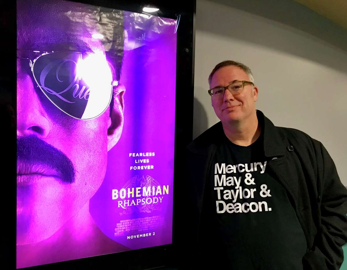 Daniel Nester, of Delmar, author of two books on the rock band Queen, stands next to a ?