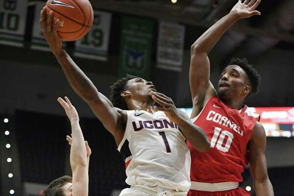 UConn's Christian Vital (1) shoots as Cornell's Jack Gordon (32) and Matt Morgan defend during the first half of an their game on Tuesday in Hartford.