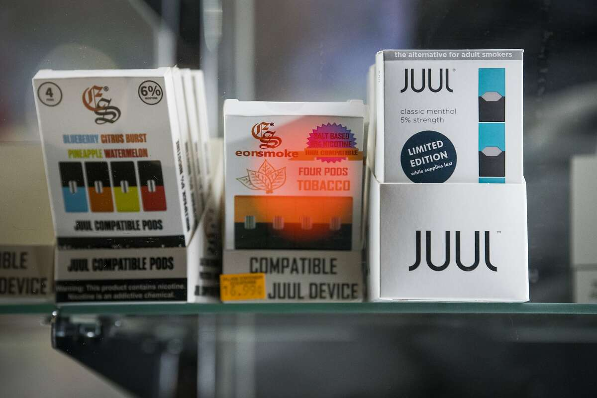 Menthol-flavored Juul e-cigarettes and other vape items in a display and for sale at a store in New York, Nov. 14, 2018. Stopping short of its threatened ban on flavored e-cigarettes, the Food and Drug Administration said on Nov. 15 that it would allow stores to continue selling the products, but only from closed-off areas that are inaccessible to minors. At the same time, the agency moved to outlaw two traditional tobacco products that disproportionately harm African Americans: menthol cigarettes and flavored cigars. (Joshua Bright/The New York Times)