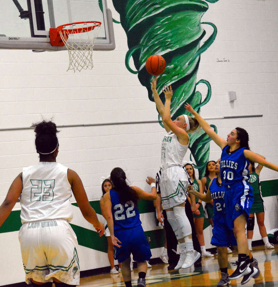 Floydada senior forward Kylie Ricketts (middle) scores a shot over Olton senior guard MacKenzie Olivarez during girls basketball action on Tuesday in Floydada. The Fillies' Carolyn Sullivan (30) tries to guard the shot while teammate Leslie Pedroza (second from right) and Lady Whirlwind Kierra Henderson (23) watch the action. Photo: Alexis Cubit/Plainview Herald